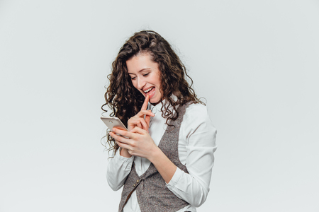 Young business lady with beautiful curly hair on a white background. During this time, he emotionally views his photos on the phone,cope space