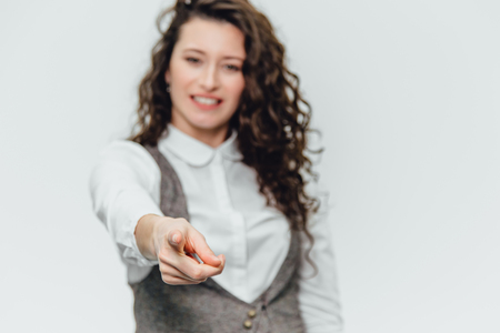Young business lady with beautiful curly hair on a white background rejoices. During this, the gesture class shows,cope space