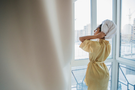 The full length of the presentation is a young woman standing by the window, enjoying the morning looking at the city after awakening in the morning. In a dressing gown with a towel on his head, resting from business, waiting for good weather. Standard-Bild