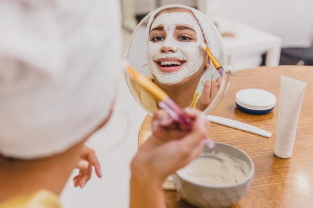 Face and body skin care, face treatment at home concept. Happy young woman applying a white mask on her face with a brush.