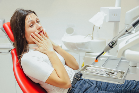 Woman at the reception of a dentist in a dental clinic. She sits in a red chair. With fear of a patient looking into the camera.