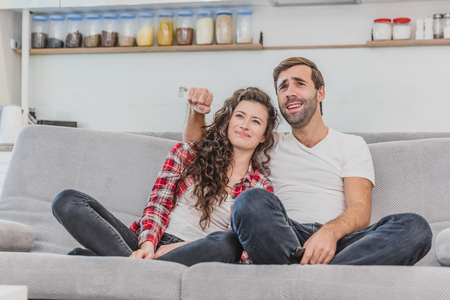 Beautiful girl and a young man sitting on the couch and watch TV. People relax on the couch.Young man in glasses and blue shirt.Young woman with glasses.