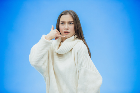 Beautiful young girl on a blue background. The girl shows a phone call with a gesture. Dressed in a white warm sweater. Has long black hair. Stock Photo