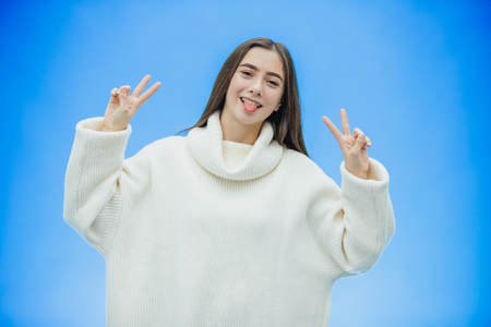 Young beautiful brunette woman on an isolated background. He raised his hands and showed a gesture with two fingers. Smiling confidently and happily. On a blue background.