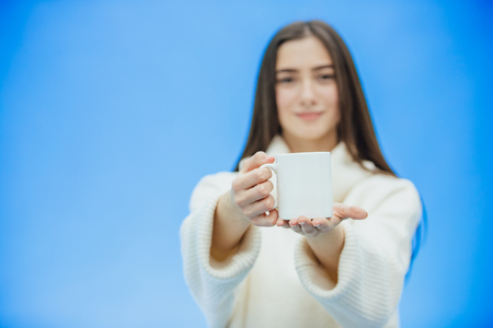 Interestingly, a young woman in a knitted white sweater. Holds a white cup of coffee or tea in his hands. Isolated against the background of a blue wall, studio portrait. Concept of a way of life of people. Фото со стока