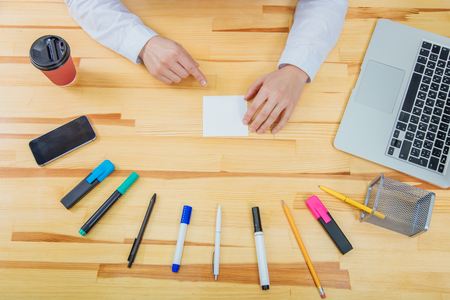 Office table with accessories: white paper, blue and pink marker, black phone, coffee cup, pen, pencil. Shows the index finger of one hand on a white sheet of paper.