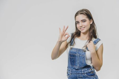 The concept of a quiet smiling beautiful young girl. A woman with soft skin pleased, the stands with her eyes turned her arms up, raising her three fingers. Wears a casual white T-shirt and denim overalls, isolated over a white wall.