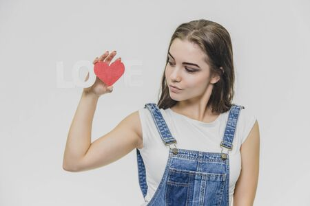 A young beautiful girl stands on a gray background. Dressed in a denim suit and a white T-shirt. Holds a sign with a word of love and looks at her. Standard-Bild