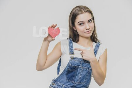 Horizontal portrait of pretty woman with puzled expression, finds solution, wears casual t shirt with denim overalls, isolated over white background. Adorable lovely female student thinks indoor
