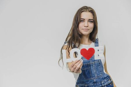 A young beautiful girl is on a gray background. Dressed in a denim suit and a white T-shirt. Holds a sign with a word of love.