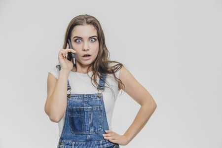A young beautiful girl dressed in a blue denim suit and a white T-shirt. She spoke on the phone with a hand on the waist and shows a very surprised facial expression.