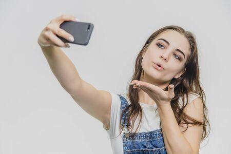 Chica guapa joven de pie sobre un fondo blanco. Vestido con un overol de mezclilla azul y una camiseta blanca. Cuando sostiene el teléfono en la mano, hace un salón.