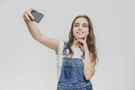 Young pretty girl standing on a white background. Dressed in a blue denim suit and a white T-shirt. Looking at the phone does the sephi. Smiling.