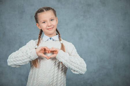 Young beautiful smart student girl shows heart and is isolated on grey background