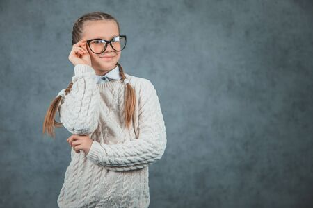 Close up photo of beautiful smiling young schoolgirl in glasses with a comfortable sweater is isolated on grey background Banco de Imagens