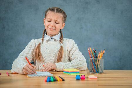La pequeña colegiala se siente desesperada y sin inspiración aislada sobre fondo gris. Foto de archivo