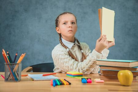 Kid with surprised face expression and stylish outfit read book and found it confusing. Stockfoto