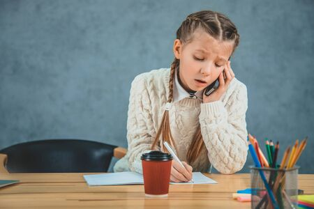 Serious schoolgirl in an uniform, with black cell near her ear a is concentrated on the work and talking. Time to create. Stock Photo