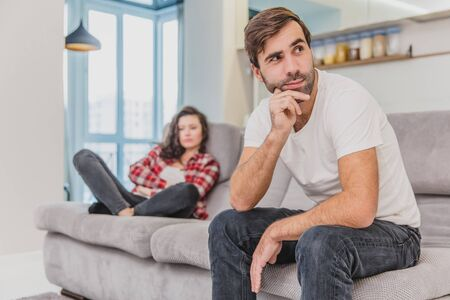 Couple argue. The wife shouted to her desperate husband, sitting on the couch in the living room at home. A man does not look at his wife.