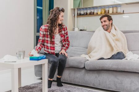 A man with a cold sitting on a sofa in a blanket blanket. Checking the temperature. The wife is sitting next to her and helps. Man at home. Sick young man Gray sofa in the room. Unhappy guy. Concept of disease. Reklamní fotografie