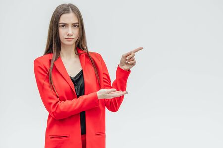 Portrait of a beautiful young brunette. Look into the camera. During this, he lifted his hands upward pointing his finger to the side. Dressed in a red jacket. Stockfoto