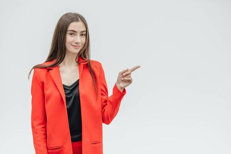 Portrait of a beautiful young brunette. Look into the camera. During this, he lifted one arm upward pointing his finger straight. Dressed in a red jacket.