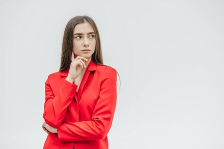 Young pretty, serious girl on a gray background. Standing with a hand on hand. Dressed in a red jacket. With black long hair.