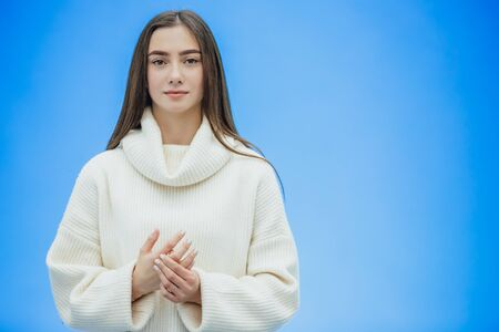 Smiling young business girl looking straight. During this, he holds his hand in his hand. Clothed in a white warm sweater. Long hair