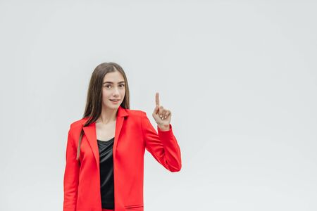 Portrait of a beautiful young brunette. Look into the camera. During this, the girl raised her hand with her index finger up. Dressed in a red jacket. Gray background.