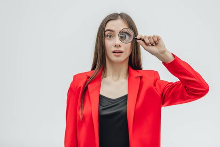Funny expressions. Shocked woman looking at magnifying glass. A surprised girl looks at opening the keys with big eyes through a magnifying glass, isolated on a white background.