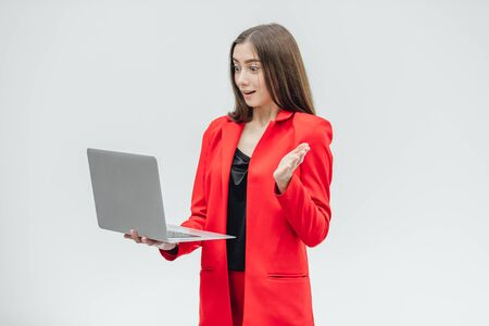 The image of a young business lady. Isolated on a gray background. Is worth it Using a gray laptop. Dressed in a red jacket.