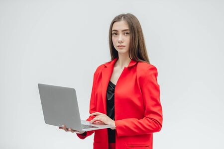 Beautiful young business woman with long hair, holding a gray notebook hand, smiling, looking into the camera. Gray background. Stockfoto