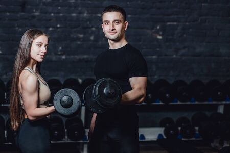 Two young guys and girls are engaged in the gym. During this they hold the weights in their hands while looking at the camera.