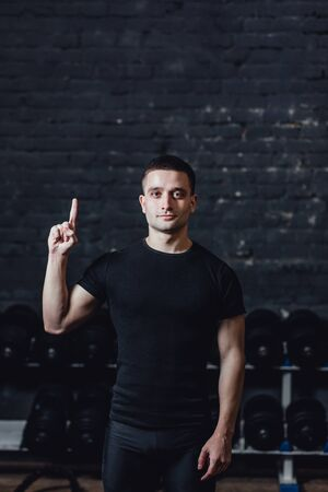 A young athlete is standing in the gym. During this dress, wear a black T-shirt. Standing on a black background and looking away. Stockfoto