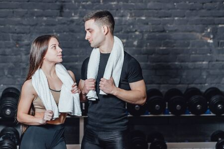 Young sporty couple guy and girl standing in gym. During this, the white scumbag is held on the neck. Stockfoto