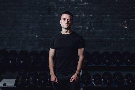 Young man in the gym. Healthcare. Lifestyle. A sexy man dressed in a black T-shirt. Caucasian Bodybuilder is nourished body. Stockfoto