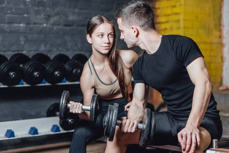 Fitness, sports, exercises and weightlifting. Concept - a young woman and a young man with dumbbells sweeping muscles in the gym. During this time they look at their muscles.