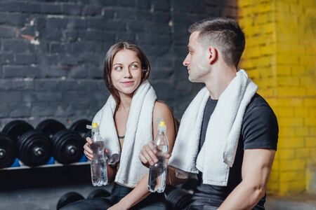 Portrait of a healthy young couple while training. Young people adhere to drinking regime during training. During this they are in the gym.