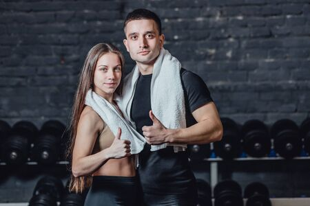 Young sporty couple guy and girl standing in gym. During this, the white scumbag is held on the neck. Standing on a black background and looking at the camera. Stockfoto