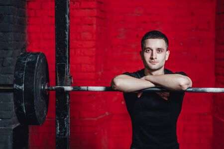 Young good guy is engaged in sports. During this time he is in the gym. Dressed in a black T-shirt. Put your hands on the barbell. Look into the camera. Stockfoto
