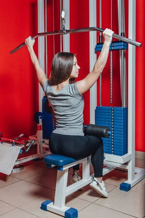 Beautiful sport girl is engaged on a simulator in the gym. Pretty girl with the beautiful tightened figure. Fitness girl in the gym Stockfoto