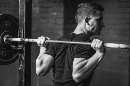 A nice muscular guy with a strong body. Exercises at the gym. Achievement of physical endurance and strength. Preparing for the competition. Stockfoto