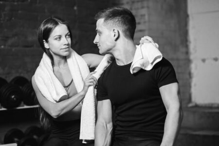 Young men and women after sports exercises. With white towels in the neck. Fitness room. Have a sports body. Stockfoto