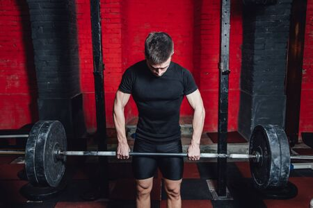 Young athlete dressed in black t-shirt. During this time, he trains crossfit to the gym. At the same time, it raises the bar with maximum effort. Stockfoto