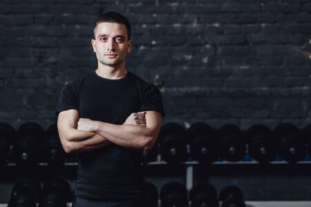A young athlete is standing in the gym. During this dress, wear a black T-shirt. Standing on a black background and looking at the camera. Stockfoto