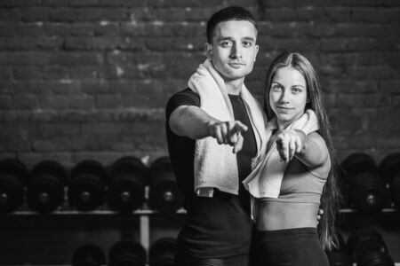 Young sporty couple guy and girl standing in gym. During this, the white scumbag is held on the neck. Standing on a black background and looking at each other. Black and white. Stockfoto