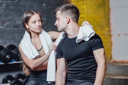 Young men and women after sports exercises. With white towels on the neck. Fitness room. Have a sporty body. See each other in the eye.