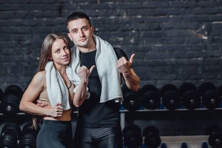 Young sporty couple guy and girl standing in gym. During this, the white scumbag is held on the neck. Standing on a black background and looking away.