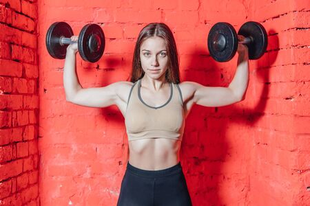 A sports woman makes an exercise weapon. Photo muscle fitness model development with dumbbells on a red background. Power and motivation