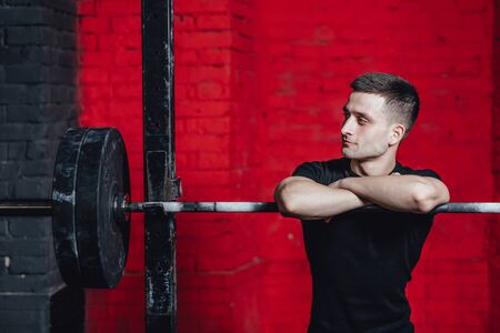 Young good guy is engaged in sports. During this time he is in the gym. Dressed in a black T-shirt. Put your hands on the barbell. Look to the side.